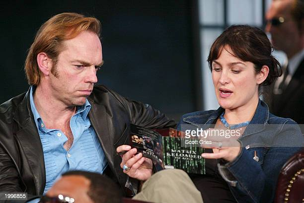 Hugo Weaving and CarrieAnne Moss look at the soundtrack for The Matrix during a visit from the cast of 'The Matrix Reloaded' on MTV's Total Request...