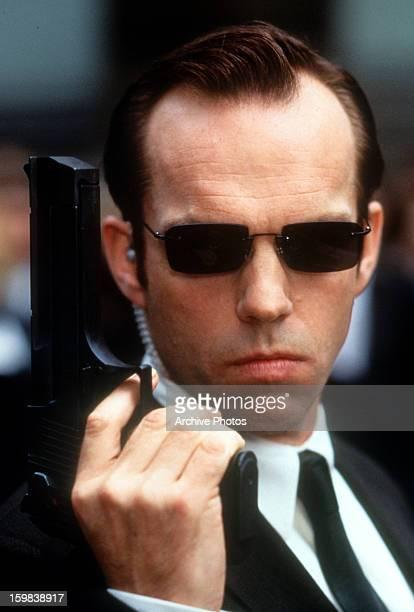 Hugo Weaving holding pistol in a scene from the film 'The Matrix' 1999