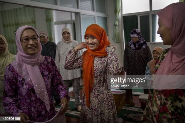 Hui Muslim female Imam Yonghua Zheng center speaks with fellow Imam Jing Ding left and worshippers at the women's only Tuanjielu Mosque on July 22...