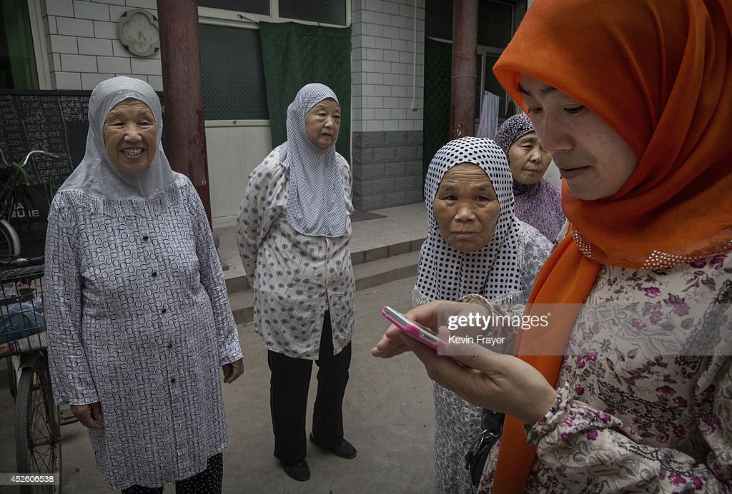 Hui Muslim female Imam Yonghua Zheng right checks messages on her phone as she chats with elderly worshippers after praying during the holy month of...