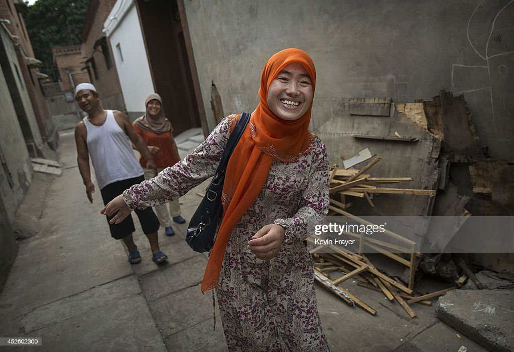 Hui Muslim female Imam Yonghua Zheng smiles as her inlaws see her off from the family home as she leaves for prayers at a women's only mosque on July...