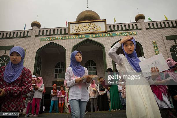 Hui Muslim girls leave a graduation for an Islamic studies course during the holy month of Ramadan at a mosque on July 22 2014 in Sangpo Henan...