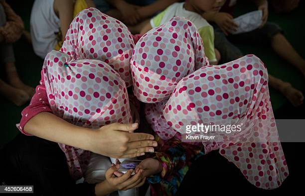 Hui Muslim girls share a smartphone as they attend a graduation for an Islamic studies course during the holy month of Ramadan at a mosqu on July 22...
