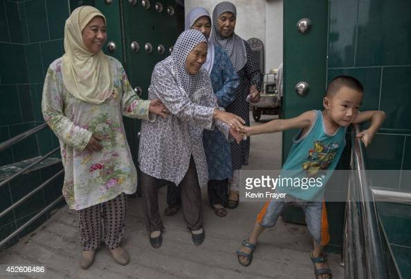 Hui Muslim women joke with a young boy after praying during the holy month of Ramadan at the women's only Tuanjielu Mosque on July 22 2014 in Qinyang...