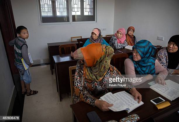 Hui Muslim women look as a boy enters their classroom during Arabic studies at the Qingzhenshang women's only Mosque on July 11 2014 in Sangpo Henan...