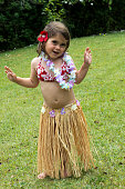 Little girl with Hawaiian Costume of a hula dancer, Hula girl dancing outdoors in the garden over green grass barefoot.