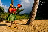 Hawaiian teenage girl dancing Hula on the beach in Kauai