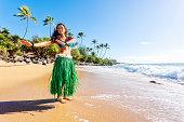 Attractive young hula dancer, dancing on a Hawaiian beach.