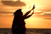 This Hawaiian hula dancer performs a hula in front of the tropical sunset.