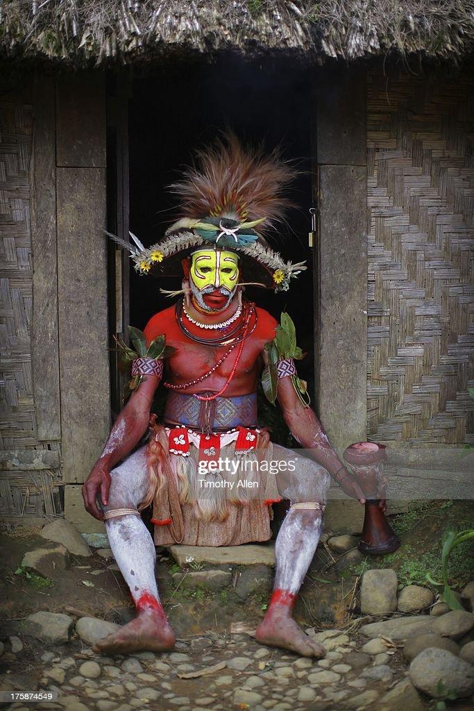 Huli Wigman sitting outside thatched hut