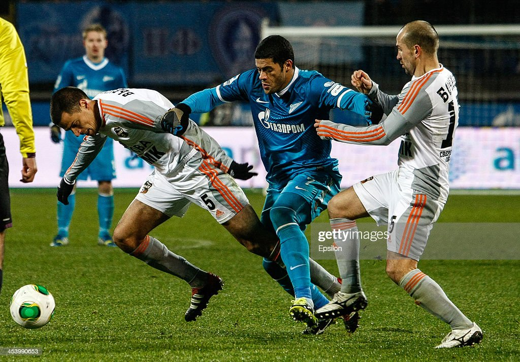 Hulk of FC Zenit St. Petersburg (C) vies for the ball with Milan Vjestica of FC Ural Sverdlovsk Oblast (L) and Andrei Bochkov of FC Ural Sverdlovsk Oblast during the Russian Football League Championship match between FC Zenit St. Petersburg and FC Ural Sverdlovsk Oblast at the Petrovsky stadium on December 6, 2013 in St. Petersburg, Russia.
