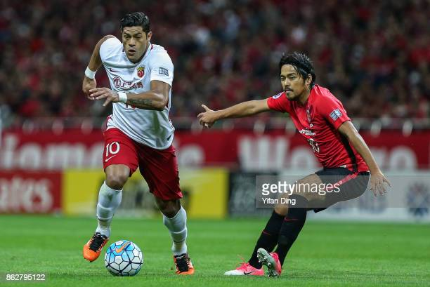 Hulk of Shanghai SIPG dribbles past Kohrogi Shinzoh of Urawa Red Diamonds during the AFC Champions League semi final second leg match between Urawa...