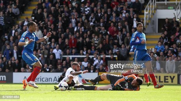 Hull City goalkeeper Steve Harper dives at the feet of Fulham's Ashkan Dejagah