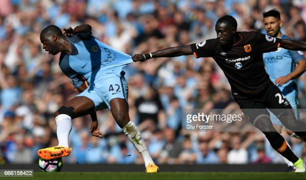 Hull City player Oumar Niasse grabs hold of Manchester City player Yaya Toure during the Premier League match between Manchester City and Hull City...