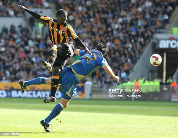 Hull City's Bernard Mendy rises above Portsmouth's Richard Hughes in a battle for the ball