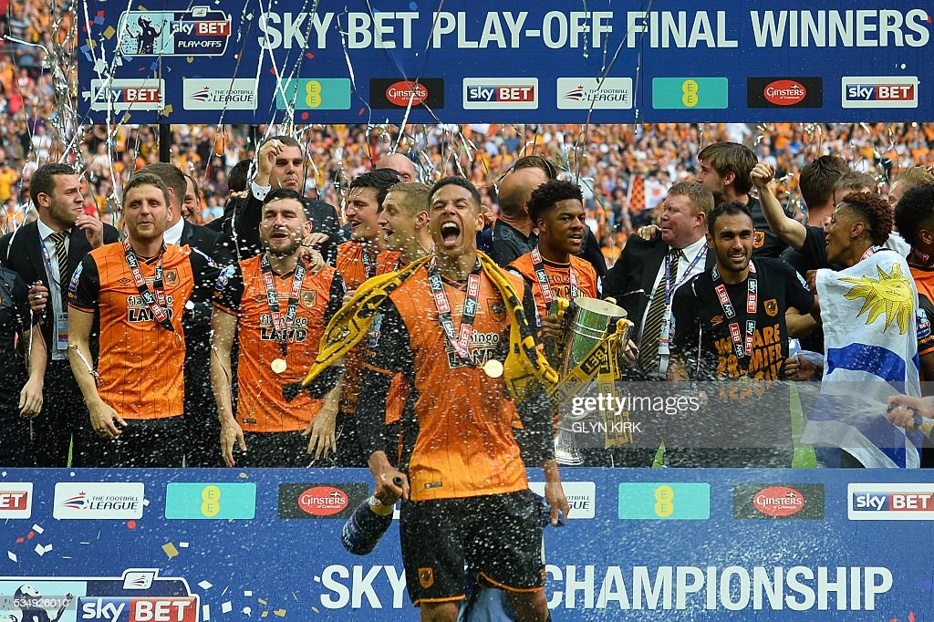 Hull City's English defender Curtis Davies (C) celebrates in front of his teammates during the presentation after Hull City won the English Championship play-off final football match between Hull City and Sheffield Wednesday at Wembley Stadium in London on May 28, 2016. Hull City secured promotion to the Premier League with a 1-0 victory in the Championship play-off final at Wembley against Yorkshire rivals Sheffield Wednesday. / AFP / GLYN
