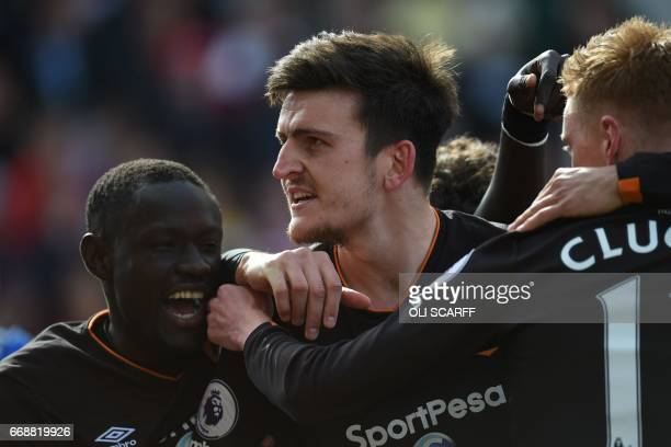 Hull City's English defender Harry Maguire celebrates with teammates scoring Hull's first goal during the English Premier League football match...