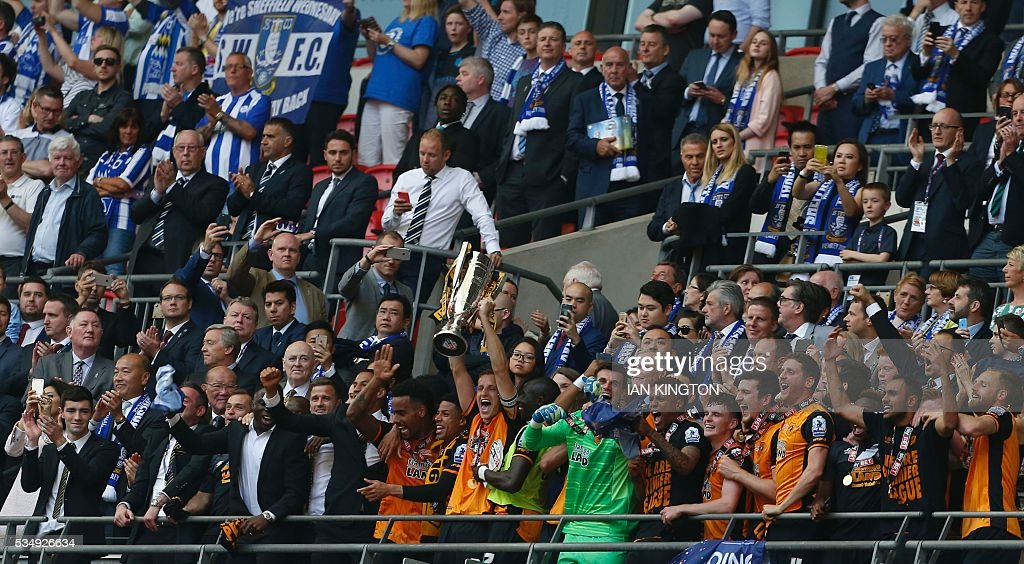 Hull City's English defender Michael Dawson (C) lifts the trophy after Hull City won the English Championship play-off final football match between Hull City and Sheffield Wednesday at Wembley Stadium in London on May 28, 2016. Hull City secured promotion to the Premier League with a 1-0 victory in the Championship play-off final at Wembley against Yorkshire rivals Sheffield Wednesday. / AFP / Ian Kington / NOT