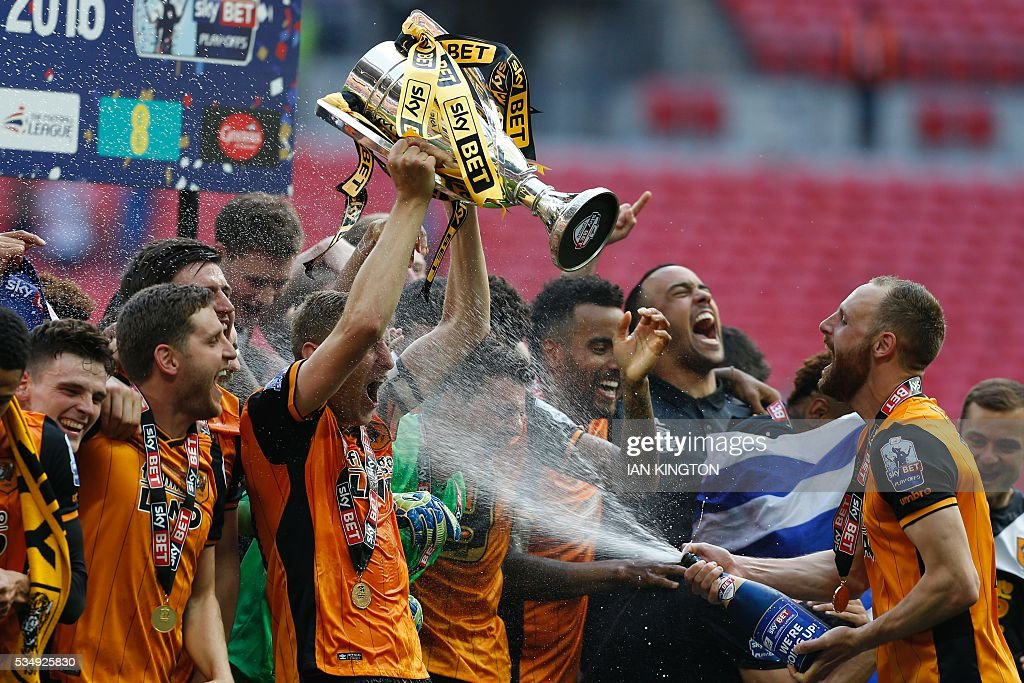 Hull City's English defender Michael Dawson (C) lifts the trophy as he is sprayed with champagn by Hull City's Irish midfielder David Meyler (R) during the presentation after Hull City won the English Championship play-off final football match between Hull City and Sheffield Wednesday at Wembley Stadium in London on May 28, 2016. Hull City secured promotion to the Premier League with a 1-0 victory in the Championship play-off final at Wembley against Yorkshire rivals Sheffield Wednesday. / AFP / Ian Kington / NOT