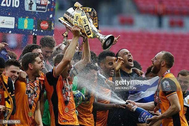 Hull City's English defender Michael Dawson lifts the trophy as he is sprayed with champagn by Hull City's Irish midfielder David Meyler during the...