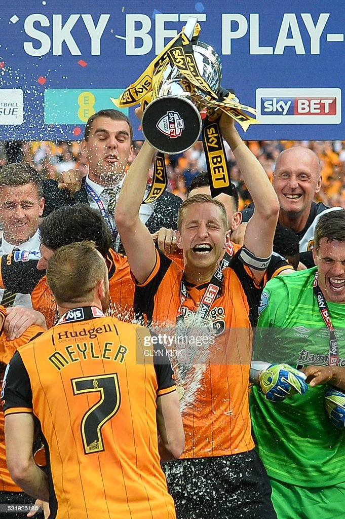 Hull City's English defender Michael Dawson (C) lifts the trophy during the presentation after Hull City won the English Championship play-off final football match between Hull City and Sheffield Wednesday at Wembley Stadium in London on May 28, 2016. Hull City secured promotion to the Premier League with a 1-0 victory in the Championship play-off final at Wembley against Yorkshire rivals Sheffield Wednesday. / AFP / GLYN