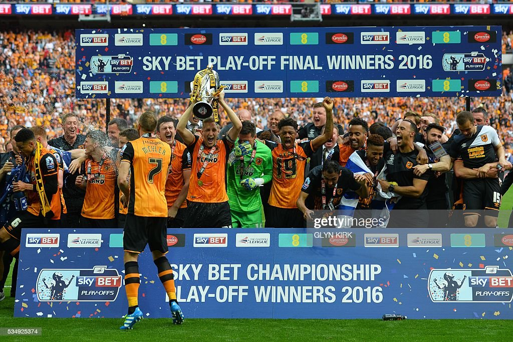 Hull City's English defender Michael Dawson (5L) lifts the trophy during the presentation after Hull City won the English Championship play-off final football match between Hull City and Sheffield Wednesday at Wembley Stadium in London on May 28, 2016. Hull City secured promotion to the Premier League with a 1-0 victory in the Championship play-off final at Wembley against Yorkshire rivals Sheffield Wednesday. / AFP / GLYN