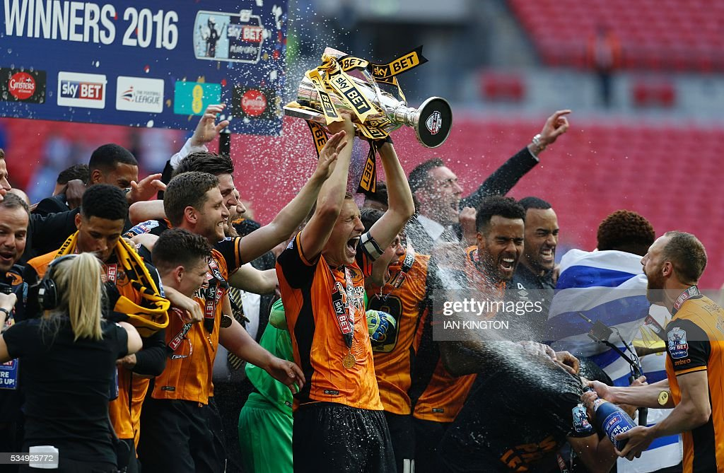 Hull City's English defender Michael Dawson (C) lifts the trophy during the presentation after Hull City won the English Championship play-off final football match between Hull City and Sheffield Wednesday at Wembley Stadium in London on May 28, 2016. Hull City secured promotion to the Premier League with a 1-0 victory in the Championship play-off final at Wembley against Yorkshire rivals Sheffield Wednesday. / AFP / Ian Kington / NOT