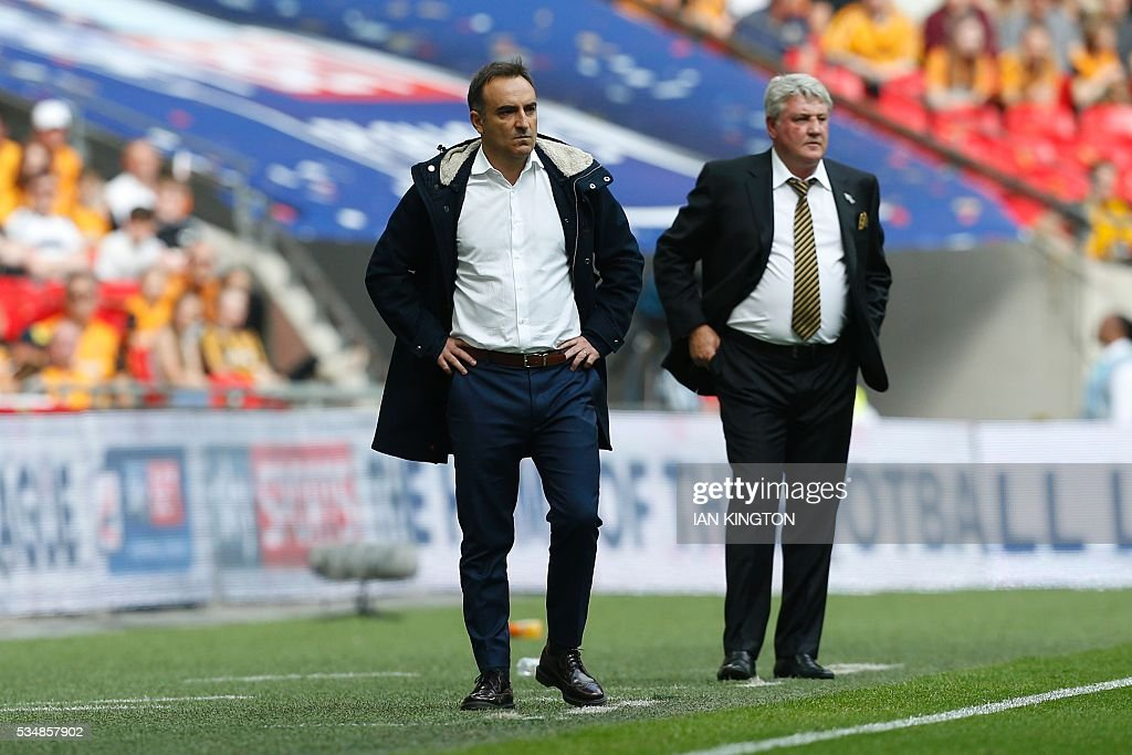 Hull City's English manager Steve Bruce (R) and Sheffield Wednesday's Portuguese head coach Carlos Carvalhal (L) watch from the touchline during the English Championship play-off final football match between Hull City and Sheffield Wednesday at Wembley Stadium in London on May 28, 2016. / AFP / Ian Kington / NOT
