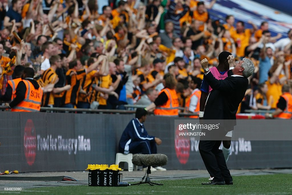 Hull City's English manager Steve Bruce (R) celebrates with the fans on the touchline after the opening goal scored by Hull during the English Championship play-off final football match between Hull City and Sheffield Wednesday at Wembley Stadium in London on May 28, 2016. / AFP / Ian Kington / NOT