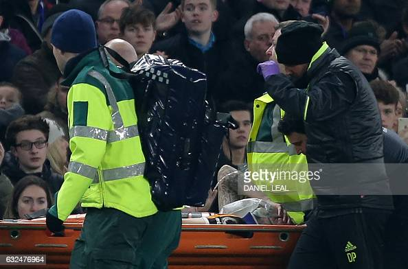 Hull City's English midfielder Ryan Mason is stretchered from the field after a clash of heads with Gary Cahill during the English Premier League...