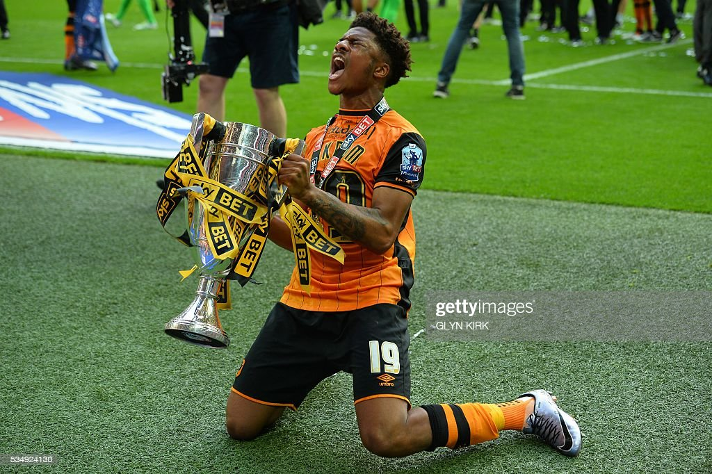 Hull City's English striker Chuba Akpom celebrates with the trophy after Hull City won the English Championship play-off final football match between Hull City and Sheffield Wednesday at Wembley Stadium in London on May 28, 2016. Hull City secured promotion to the Premier League with a 1-0 victory in the Championship play-off final at Wembley against Yorkshire rivals Sheffield Wednesday. / AFP / GLYN