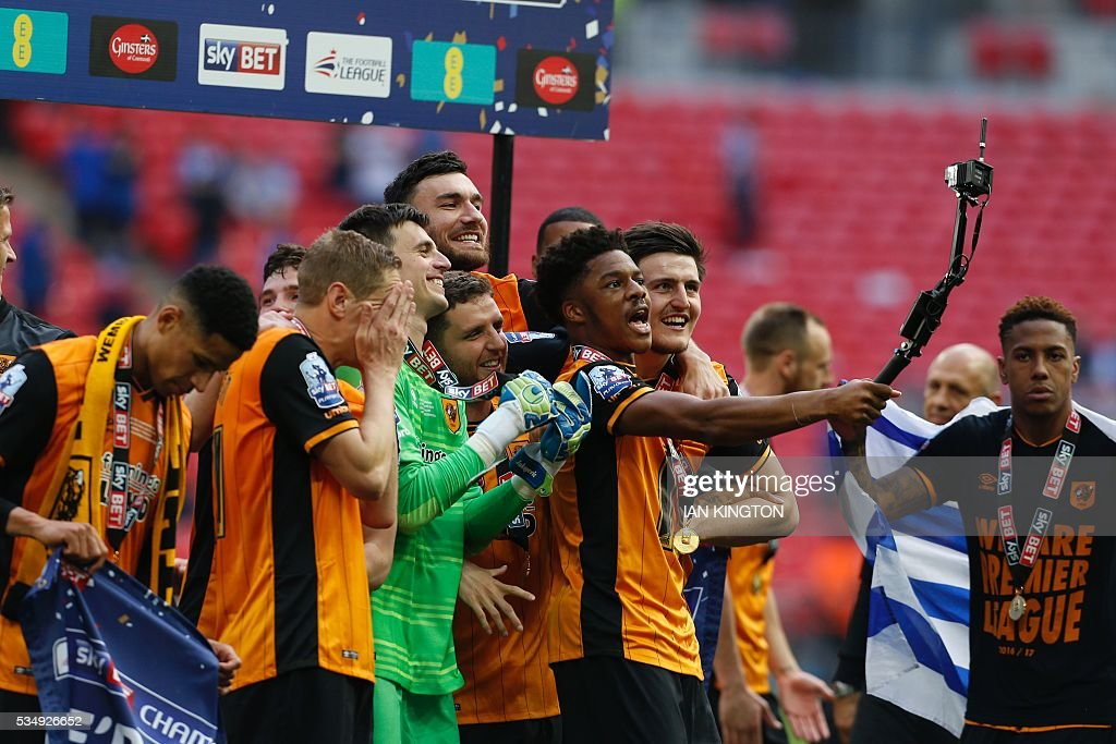 Hull City's English striker Chuba Akpom (C) takes a selfie during the presentation after Hull City won the English Championship play-off final football match between Hull City and Sheffield Wednesday at Wembley Stadium in London on May 28, 2016. Hull City secured promotion to the Premier League with a 1-0 victory in the Championship play-off final at Wembley against Yorkshire rivals Sheffield Wednesday. / AFP / Ian Kington / NOT