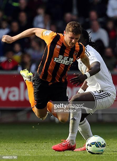 Hull Citys Englishborn Northern Irish defender Alex Bruce vies with Swansea City's French striker Bafetimbi Gomis during the English Premier League...
