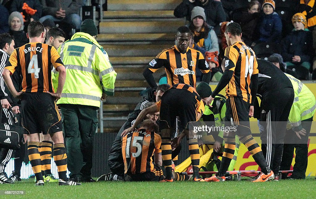 Hull City's Irish defender Paul McShane (C #15) receives attention before being stretchered off the pitch injured after a heavy tackle during the English Premier League football match between Hull City and Southampton at the KC Stadium in Hull, north-east England, on February 11, 2014. AFP PHOTO / LINDSEY PARNABY USE. No use with unauthorized audio, video, data, fixture lists, club/league logos or live services. Online in-match use limited to 45 images, no video emulation. No use in betting, games or single club/league/player publications.