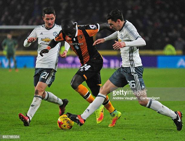Hull City's Oumar Niasse vies for possession with Manchester United's Ander Herrera left and Manchester United's Matteo Darmian during the EFL Cup...