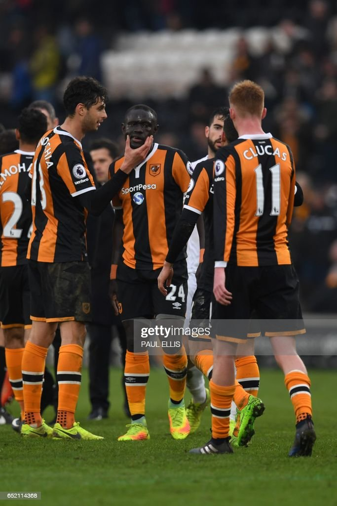 Hull City's Senegalese striker Oumar Niasse (C) celebrates with teammates on the pitch after the English Premier League football match between Hull City and Swansea City at the KCOM Stadium in Kingston upon Hull, north east England on March 11, 2017. Niasse scored both goals as Hull won the game 2-1. / AFP PHOTO / Paul ELLIS / RESTRICTED TO EDITORIAL USE. No use with unauthorized audio, video, data, fixture lists, club/league logos or 'live' services. Online in-match use limited to 75 images, no video emulation. No use in betting, games or single club/league/player publications. /