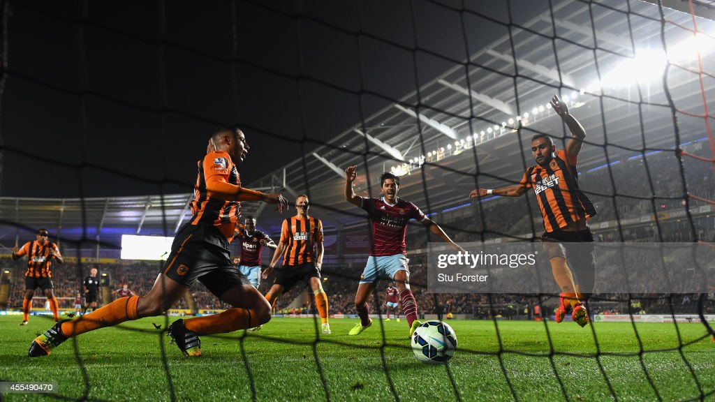Hull defenders look on as West Ham defender James Tomkins (c) celebrates the second West Ham goal during the Barclays Premier League match between Hull City and West Ham United at KC Stadium on September 15, 2014 in Hull, England.