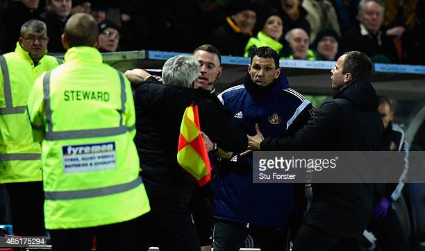 Hull manager Steve Bruce is held back by the assistant referee as he and Sunderland manager Gus Poyet argue after Poyet is sent to the stand during...