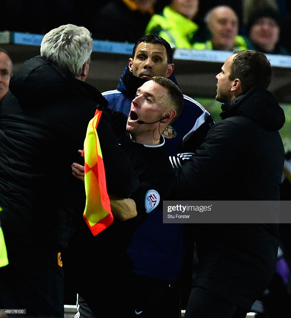 Hull manager Steve Bruce (l) is held back by the assistant referee as he and Sunderland manager Gus Poyet argue after Poyet is sent to the stand during the Barclays Premier League match between Hull City and Sunderland at KC Stadium on March 3, 2015 in Hull, England.