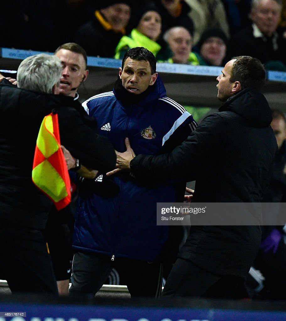 Hull manager Steve Bruce (l) is held back by the assistant referee as he and Sunderland manager Gus Poyet (held back by Stephen Clemence (r) argue after Poyet is sent to the stand during the Barclays Premier League match between Hull City and Sunderland at KC Stadium on March 3, 2015 in Hull, England.