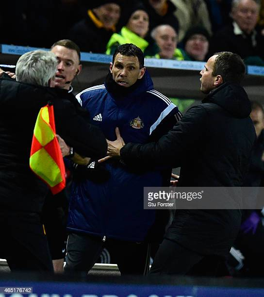 Hull manager Steve Bruce is held back by the assistant referee as he and Sunderland manager Gus Poyet held back by Stephen Clemence argue after Poyet...