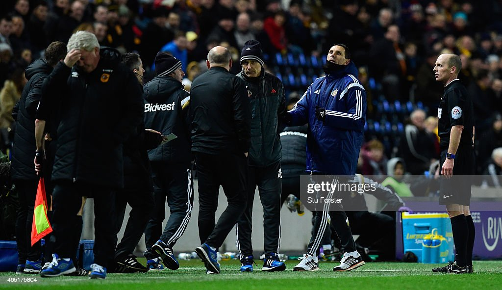 Hull manager Steve Bruce (l) looks away as Sunderland manager Gus Poyet (2nd right) argues after Poyet is sent to the stand during the Barclays Premier League match between Hull City and Sunderland at KC Stadium on March 3, 2015 in Hull, England.