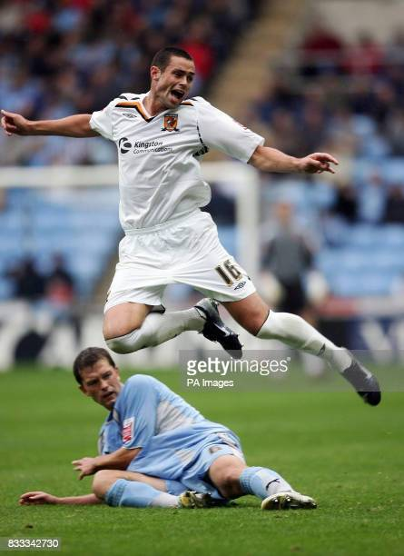Hull's Damien Delaney clears a challenge from Coventry's Stephen Hughes during the CocaCola Football League Championship match at Ricoh Arena Coventry