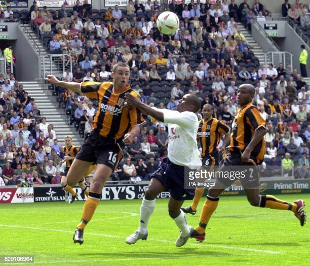 Hull's Damien Delaney heads clear under pressure from Spurs' Jermain Defoe as fellow Hull city player'tiger' Alton Thelwell looks on during the...