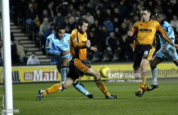 Hull's Ian Ashbee clears whilst under pressure from Mansfield's Iyseden Christie as Hull teammate Damien Delaney looks on during their Nationwide...