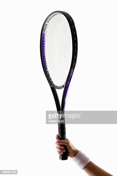 A human arm holding a tennis racket up