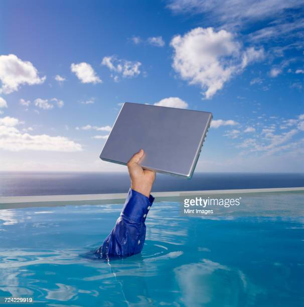 Human arm in blue shirt sleeve in swimming pool, holding aloft a laptop computer, sky and clouds.