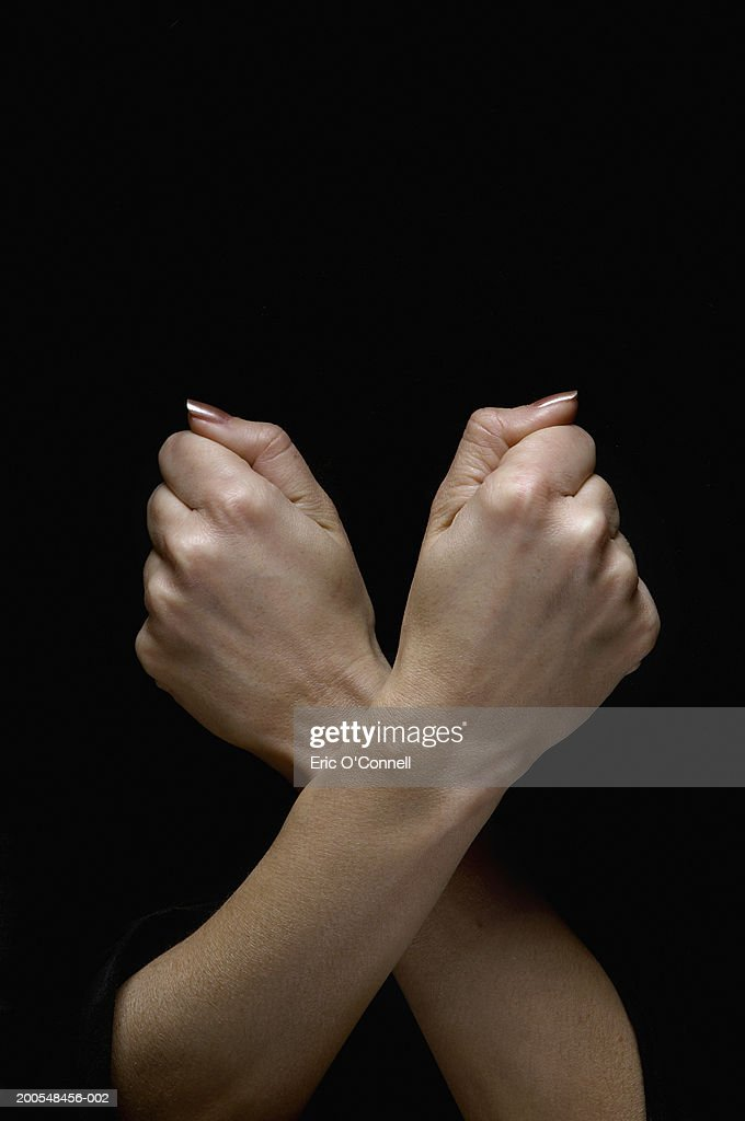 Human arms crossed, making fist, close-up, (digital composite)