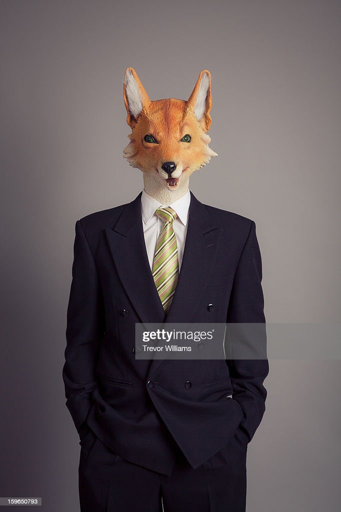 A human figure with a fox head wearing a suit : Stock Photo