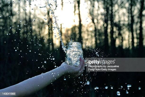 Human had splashing water from mason jar